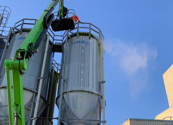 cleaning top of silo in cherry picker