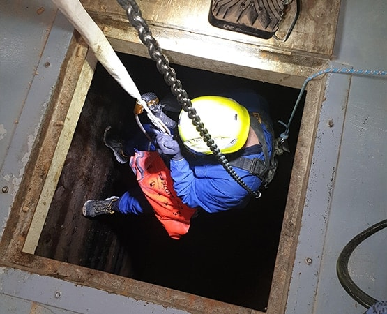 technician entering confined hole with rope